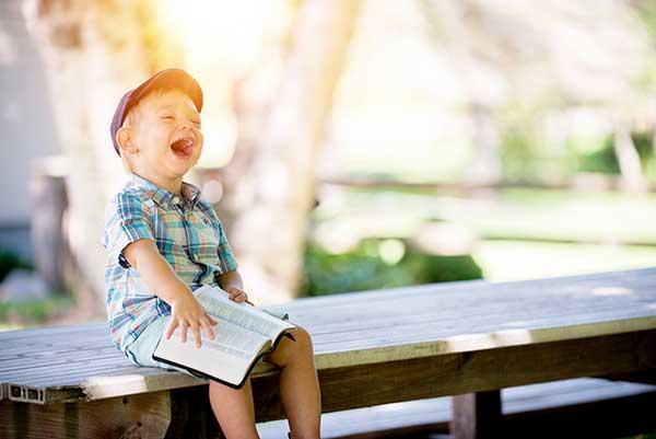 jeune enfant souriant assis sur un banc avec un livre