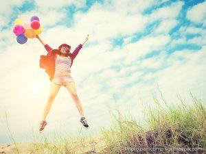 personne qui saute heureuse avec des ballons sur une plage